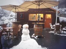 Eine kleine Holzhütte, davor eine Bank, Tisch und Stühle, der Schnee ist gekehrt und ein Schneeman daraus gebaut
